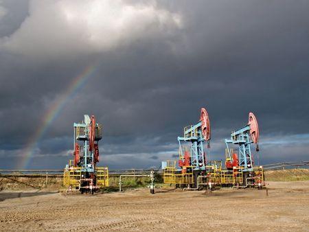 Rainbow under oil pumps. Siberia. Stock Photo