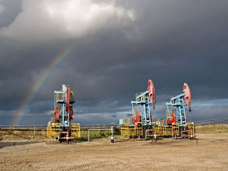 Rainbow under oil pumps. Siberia. Stock Photo