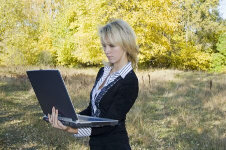 Business women with laptop. Workplace in autumn forest Stock Photo - 4040283