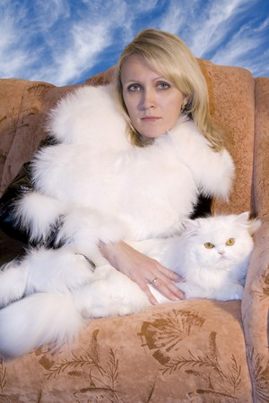 Beatiful woman with white cat sitting on sofa photo