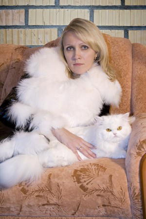 Beatiful woman with white cat sitting on sofa near a brick wall . Grange style photo