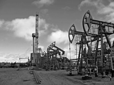 Work of oil industry. Construction and equipment of pump jack. Black and white photo