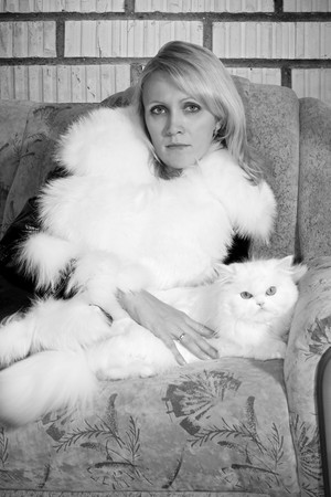 Beatiful woman with white cat near a brick wall . Grange style . Black and white photo photo