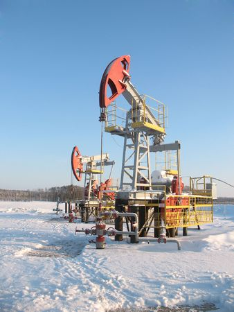 Oil pump jack in work. Oil industry in West Siberia. Siberian frost in sunny day.