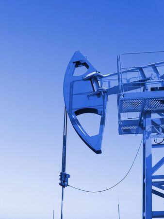 Oil pump jack in work. Oil industry in West Siberia. Siberian frost in sunny day. Blue filter  Stock Photo