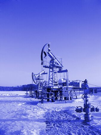 Oil pump jack in work. Oil industry in West Siberia. Siberian frost in sunny day. Colorize in blue  photo