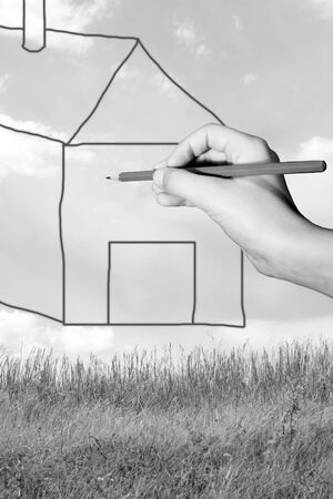 Young boy draw a house on a beautiful lawn photo