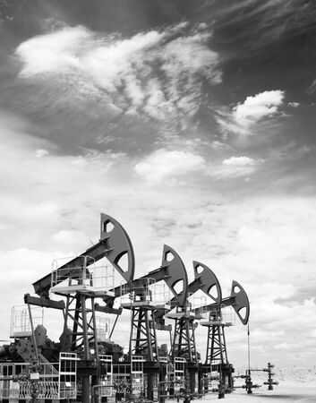 Pump jacks on a oil field. Black and white photo Stock Photo
