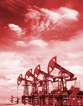 Pump jacks on a oil field. Colorize in red