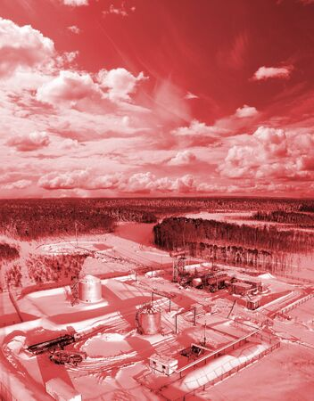 Construction site in wild winter forest. Building of petrochemical object. red filter photo