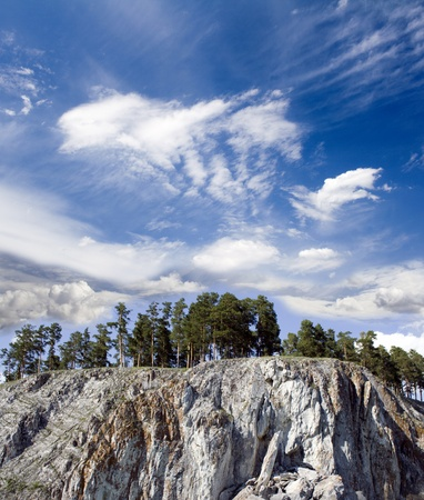Pines on a rock. Blue sky above mountain photo