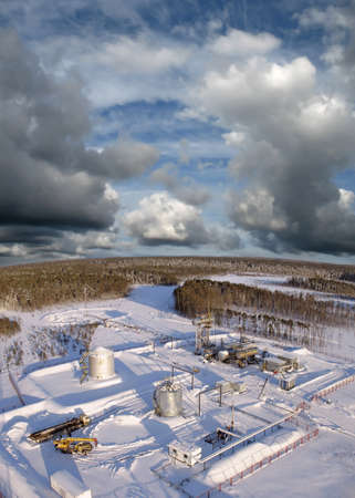 Oil and gas industry. Work of oil pump jack on a oil field.. Construction site in wild winter forest. Building of petrochemical plant. Panoramic view photo