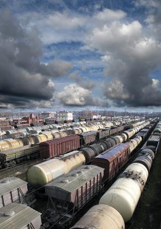 ferrocarril: Coches de ferrocarril en una estaci�n de ferrocarril. Transporte de carga. Nubes de tormenta sobre el tren