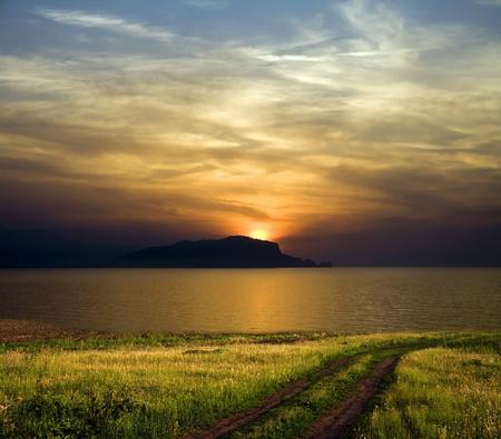 Road to sea. Sunset above mountain. Beautiful autumn landscape.