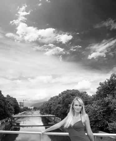 ifestyle: Beautiful young woman in red dress stay on a bridge. Summer portrait. Black and white photo