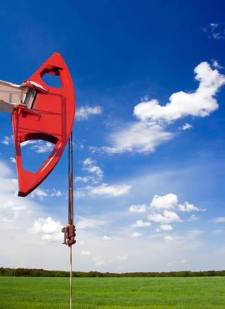 Oil and gas industry. Work of oil pump jack on a oil field. Oil pump on a beatiful meadow. Problem of ecology  photo