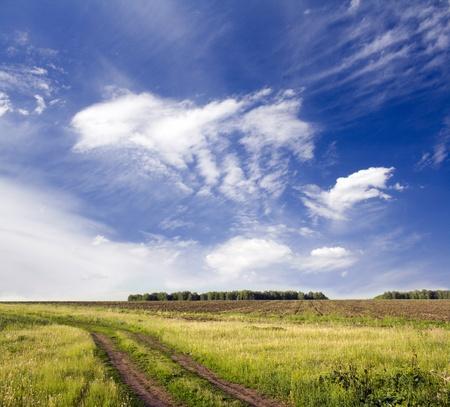 Mooie zomer landschap. Blauwe lucht met witte wolken boven de landelijke baan