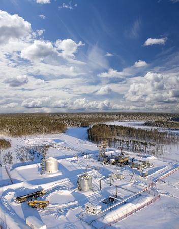Olie-en gasindustrie. Werk van oliepomp ingang van een olieveld .. Bouw in het wild levende winterbos. De bouw van petrochemische object Stockfoto