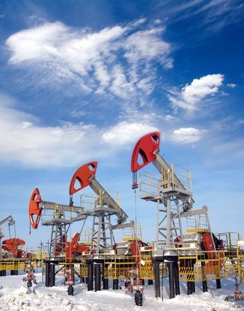 Olie-en gasindustrie. Werk van oliepomp aansluiting op een olieveld. Witte wolken en de blauwe lucht boven olieveld