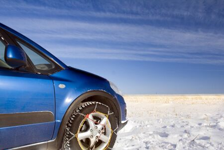 Winter off road travel. Blue car drivinig on a snow field. Snow chains. Blue sky above frozen field photo