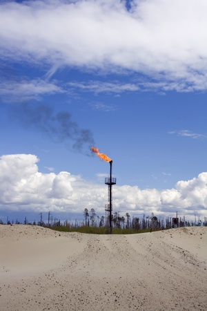 Work of oil and gas industry. Flame torch. Colorful blue sky with white clouds Stock Photo