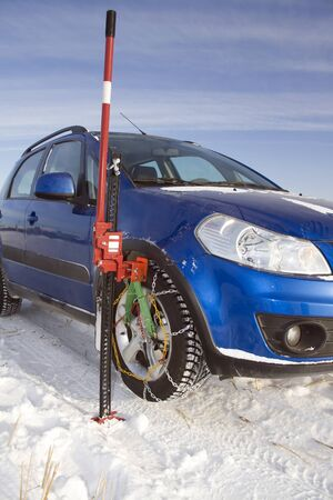 Rescue of the car which have got stuck in a snow with the help a farm jack. Winter off road travel photo