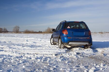 Blue car on a snow field. Winter travel Stock Photo - 17644404