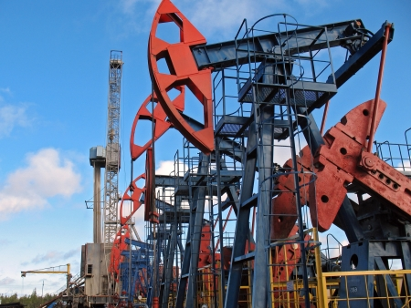 Oil and gas industry. Work of oil pump jack on a oil field. Borehole drilling oil well photo