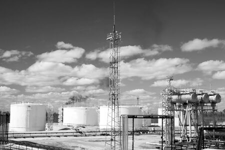 Oil industry and gas industry. Work of refinery petrochemical plant. Oil reservoir and storage tank of mineral oil. Flame torch. Black and white photo photo