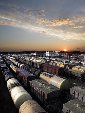 express lane: Railroad cars on a railway station. Cargo transportation. Work of industry. Urban scene. Beautiful sunset.