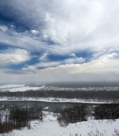 Winter landscape. Gray snowy forest and blue sky with white clouds. Cold river photo