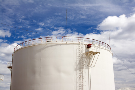 Oil reservoir and blue sky with clouds. Oil industry and gas refinery plant. Industrial scene of oil field Stock Photo
