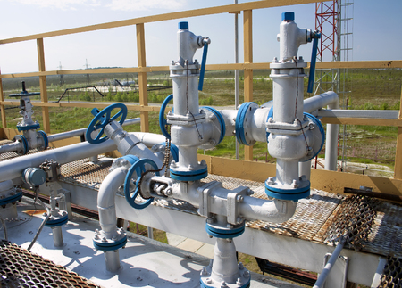 oil barrel: V�lvulas de grupo controlan la producci�n de petr�leo en la planta de refiner�a de petr�leo y gas. Sector de Petr�leo Foto de archivo