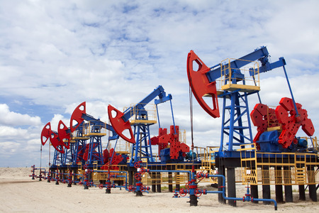 Gas and oil industry. Work of oil pump jack on a oil field. White clouds, blue sky, desert.r