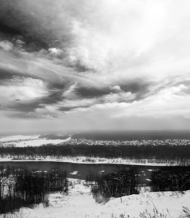 Winter landscape. Gray snowy forest and blue sky with white clouds. Cold river. Black and white photo photo