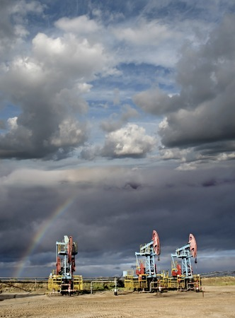 oil and gas industry: Storm and rainbow over oil pumps. Oil field. Gas industry.