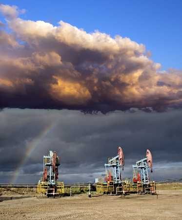 oil and gas industry: Oil industry. Storm and rainbow over oil pumps. Oil field. Gas industry.
