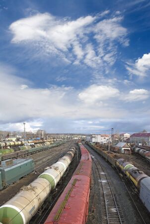 goods train: Railway station. Cargo transportation of goods by rail. Train with storage tank. Blue sky and white clouds