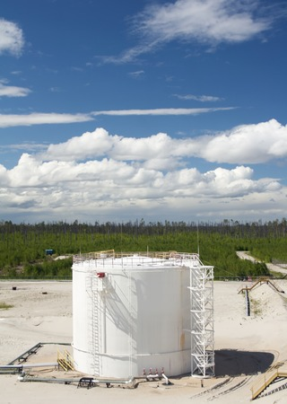 Oil reservoir. Oil and gas refinery plant. Industrial scene of oil field. Blue sky with clouds above gas station.