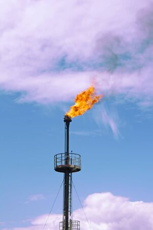 Gas flame torch. Work of gas station. Ecology and pollution. Colorful clouds