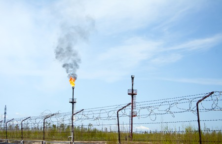 Oil reservoir and flame torch. Oil refinery plant. Gas station