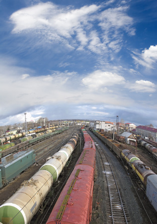 Railway station. Cargo transportation of goods by rail. Train with storage tank. Blue sky and white clouds