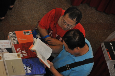 scholars: men reading book in the book fair