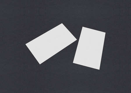 Blank white Business card mockup stacks at grey textured paper background.