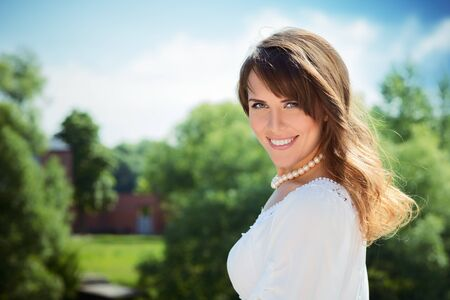 Smiling long haired young woman in white tunic and pearls necklace looking at camera trees and mansion in background Stock Photo