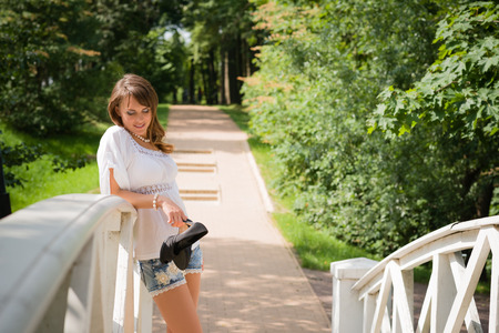 Smiling long haired young woman in white tunic and cutoffs leaning against a white plank bridge railing and looking downwards stilettos in hand trees and paved road in background