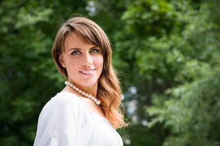 Smiling long haired young woman in white tunic and pearls necklace looking at camera trees in blurry background Stock Photo