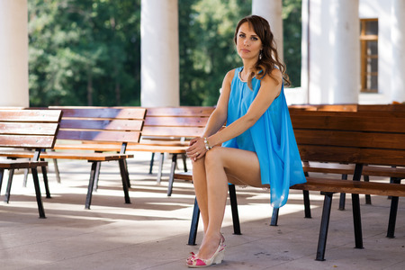 young woman sitting on bench and looking at camera