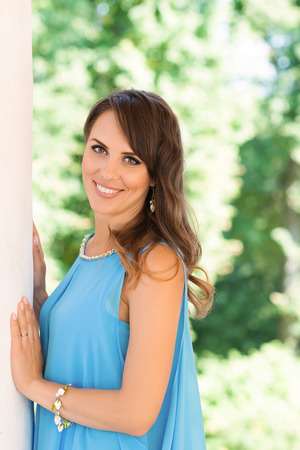 eyes hazel: Smiling young woman leaning on column and looking at camera. Stock Photo