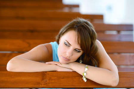 hazel eyes: Young smiling woman looking away and resting chin on palm, leaning on bench. Stock Photo